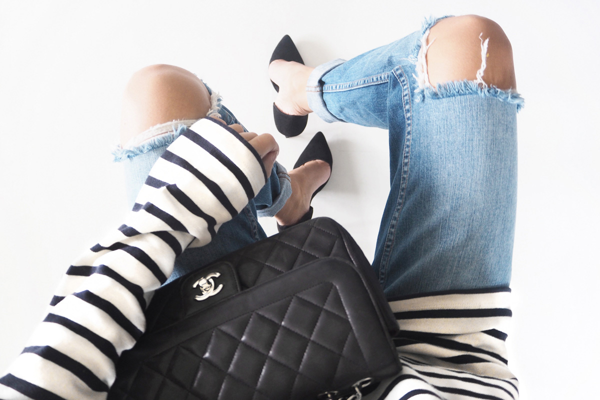 sitting with chanel bag with striped top and distressed jeans