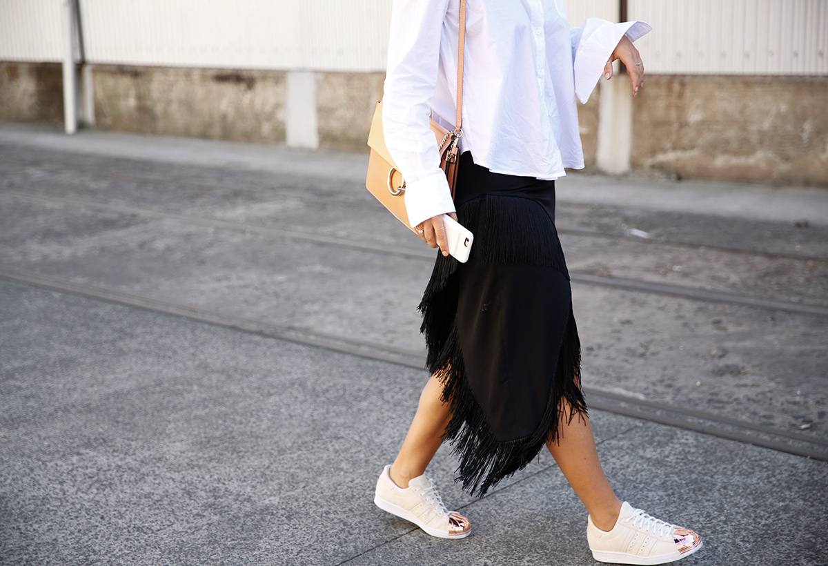 walking to fashion week show in fringe skirt with phone