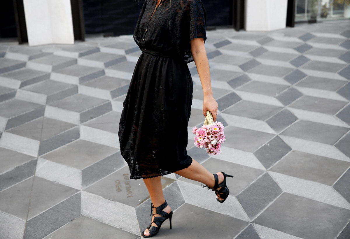 walking through Eastland with a bunch of pink flowers in a black lace dress