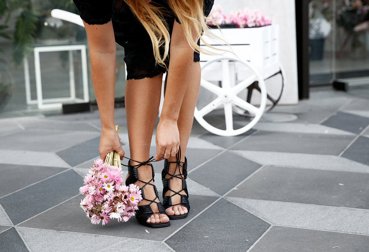 blogger bending down to tie up shoes with bouquet of flowers