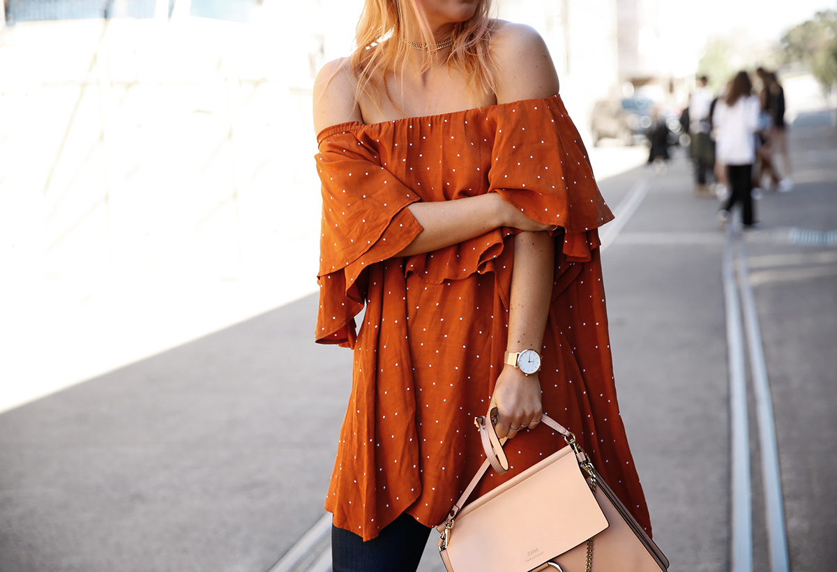 at fashion week in off the shoulder dress