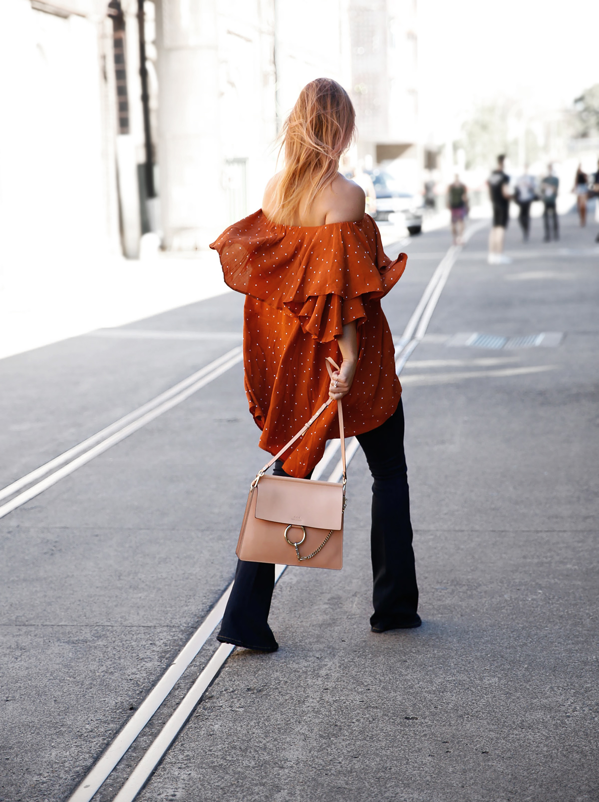 leaving fashion week in off shoulder dress and flared jeans