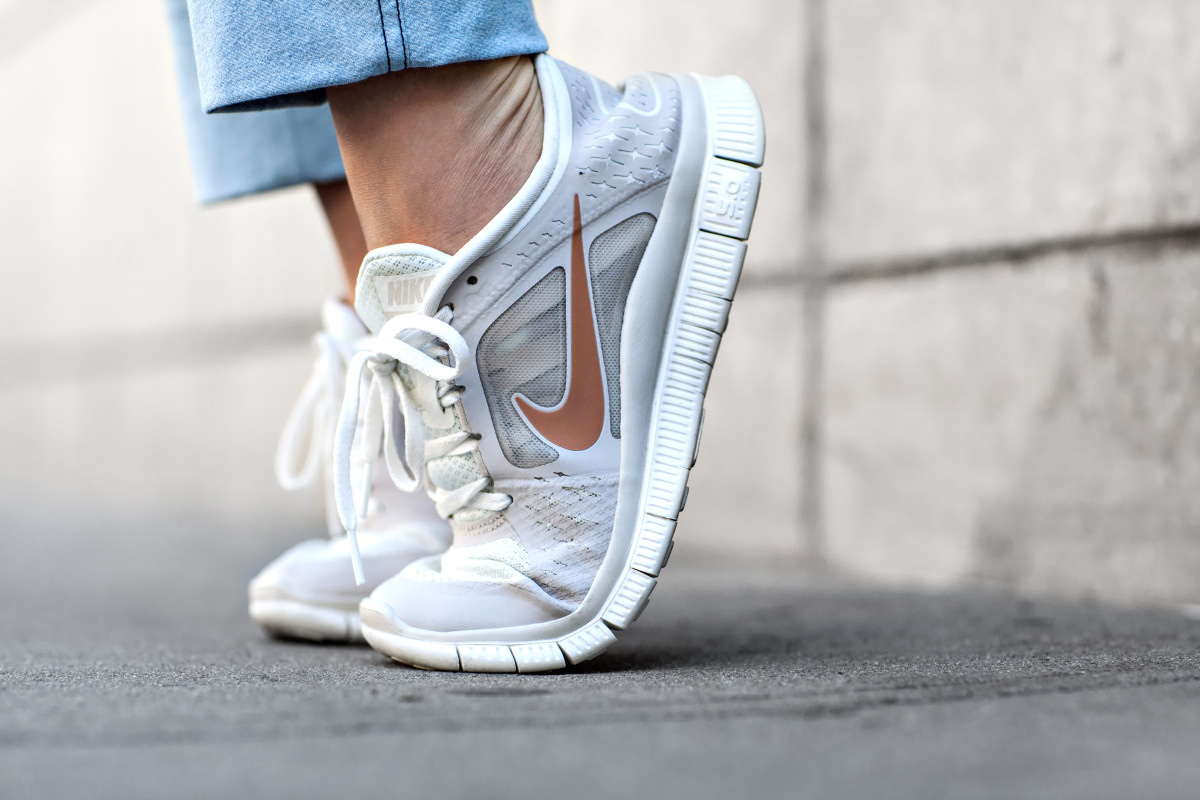 wearing white and gold nike free run sneakers with denim blue jeans