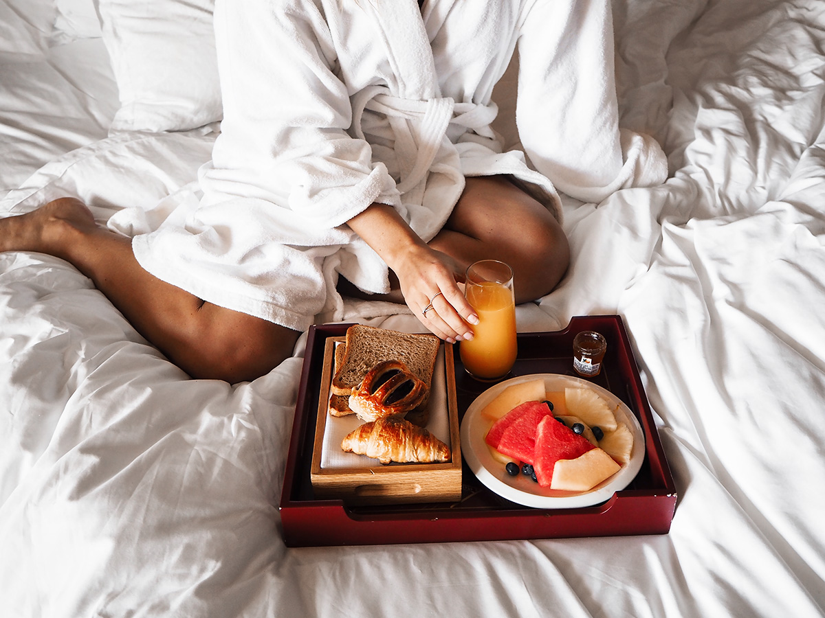 Blogger Lisa Hamilton from See Want Shop eating breakfast in bed at The Intercontinental Shanghai Ruijin hotel