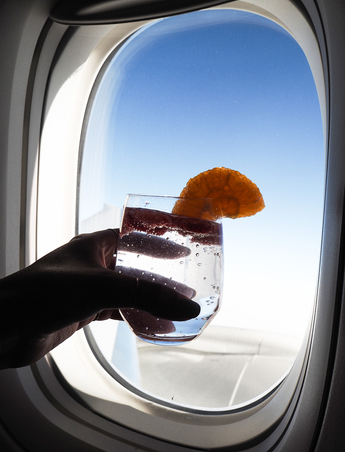 Travel blogger Lisa Hamilton for See Want Shop in Etihad Airway's business class cabin drinking a cocktail