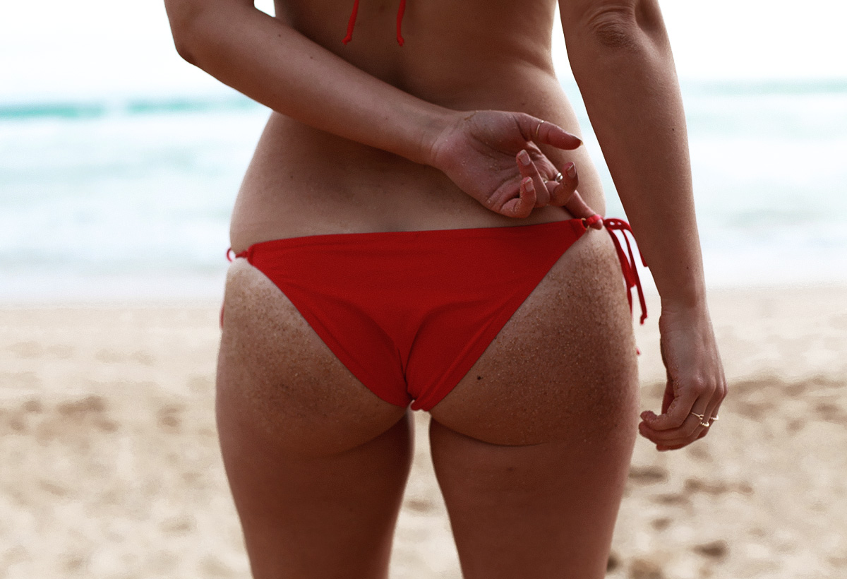 Fashion & travel blogger Lisa Hamilton from See Want Shop wearing a L'Agent by Agent Provocateur red string bikini bottom at the beach in Australia