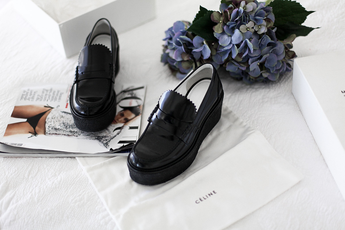 Style blogger Lisa Hamilton styles Celine black platform loafers from Yoox online store