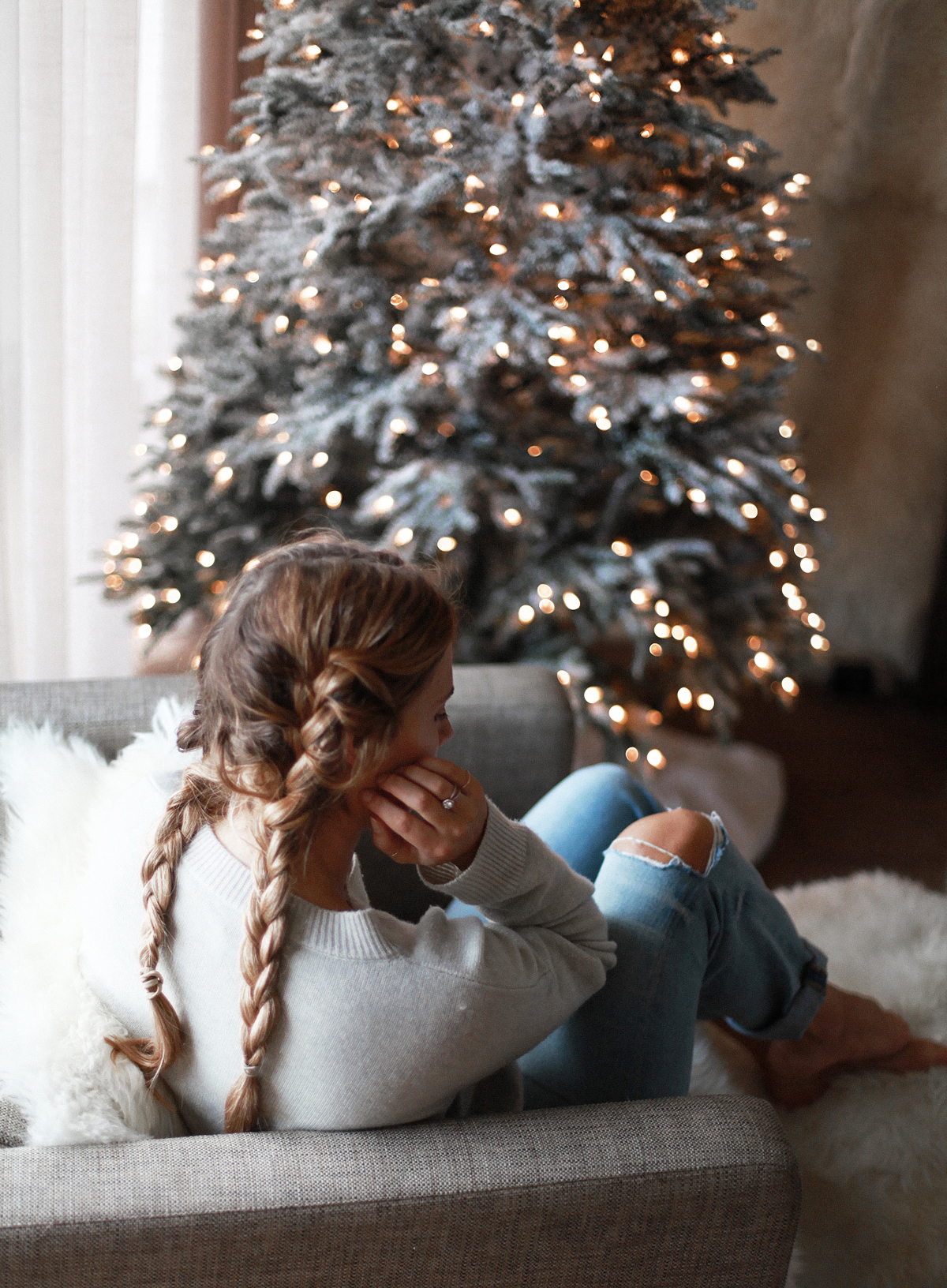Lifestyle blogger Lisa Hamilton from See Want Shop with her Christmas tree wearing denim jeans, braided hair & knit sweater
