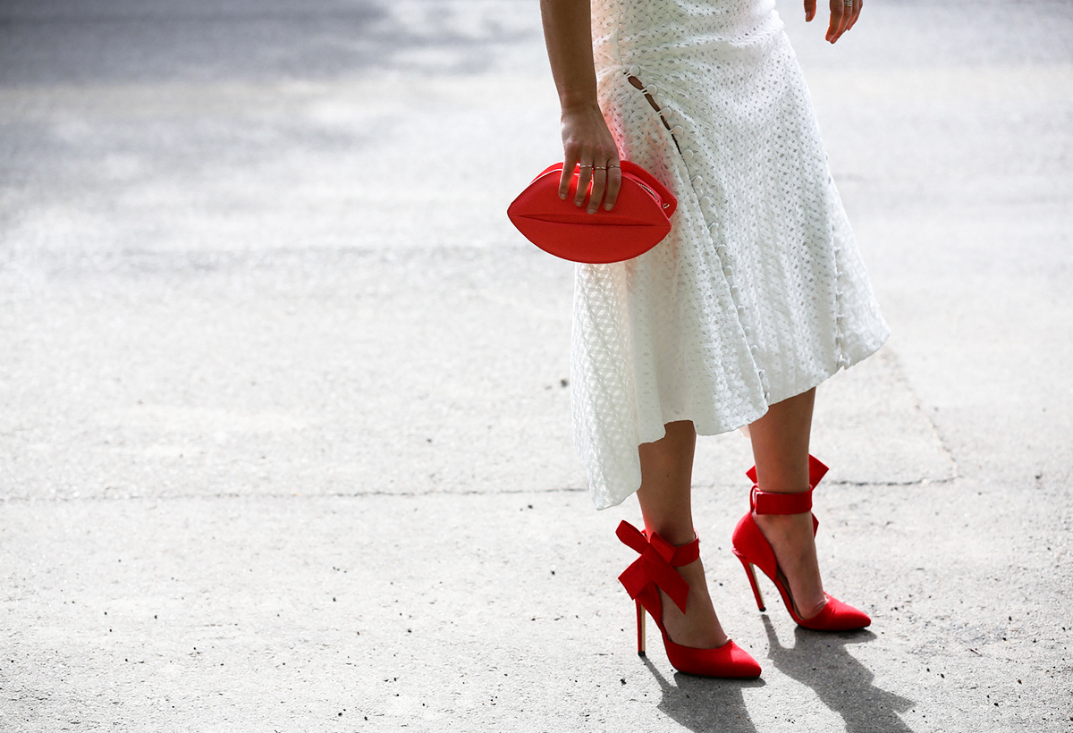Fashion blogger Lisa Hamilton from See Want Shop styling a red lippy clutch with bow heels this Christmas