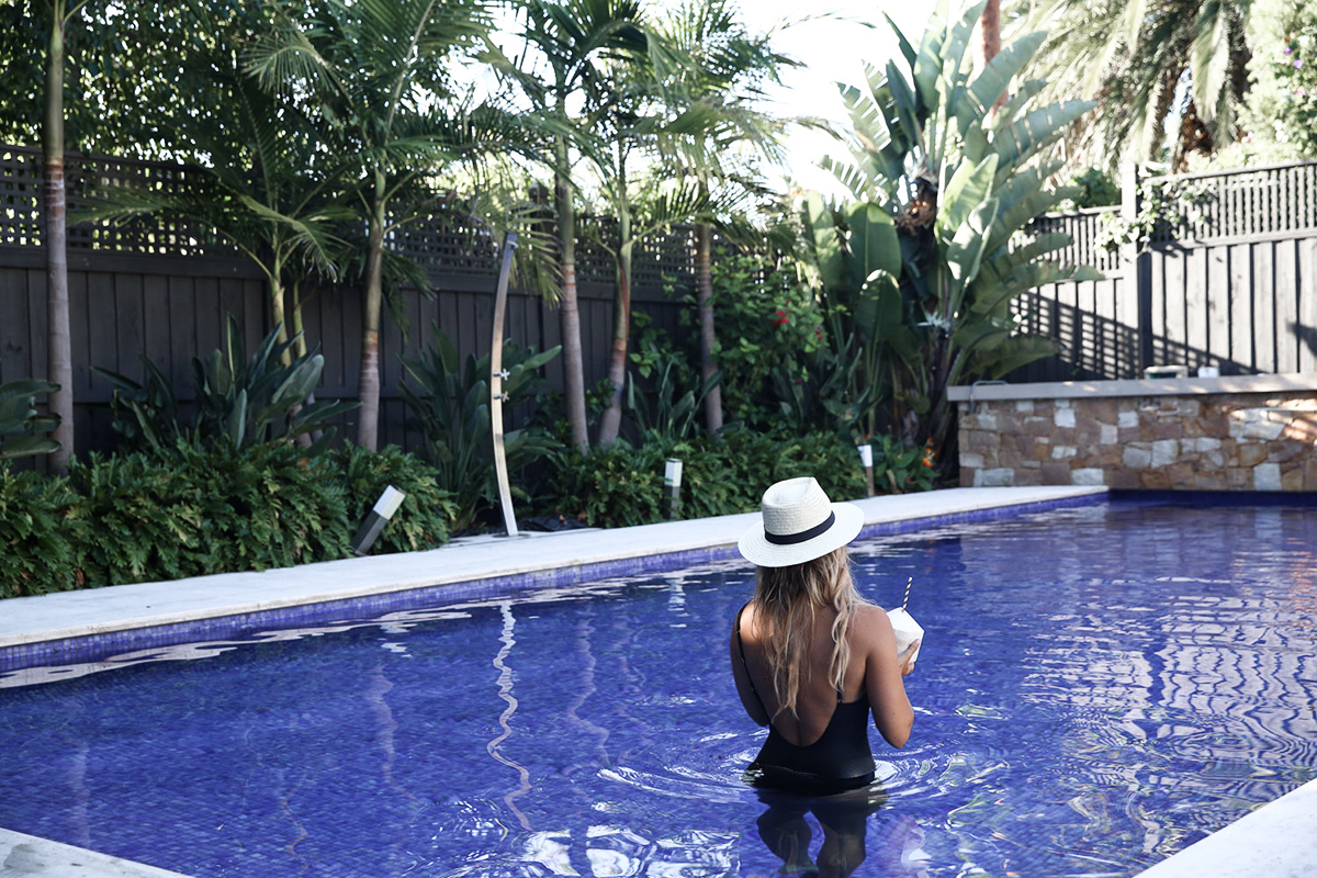 Lifestyle blogger Lisa Hamilton from See Want Shop wearing backless lace-up swimsuit from Marks & Spencer & straw panama hat during summer