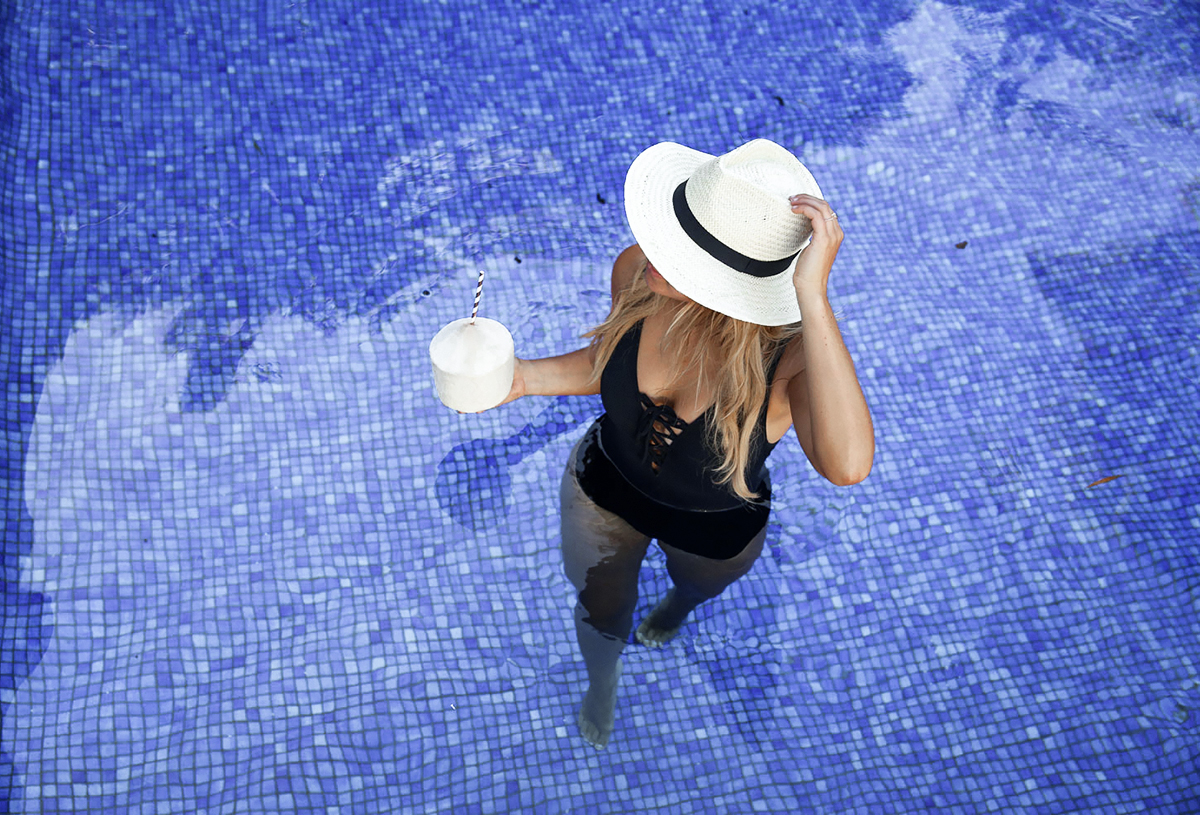 Lifestyle blogger Lisa Hamilton from See Want Shop wearing black lace-up swimsuit with straw panama hat from Marks & Spencer in the pool