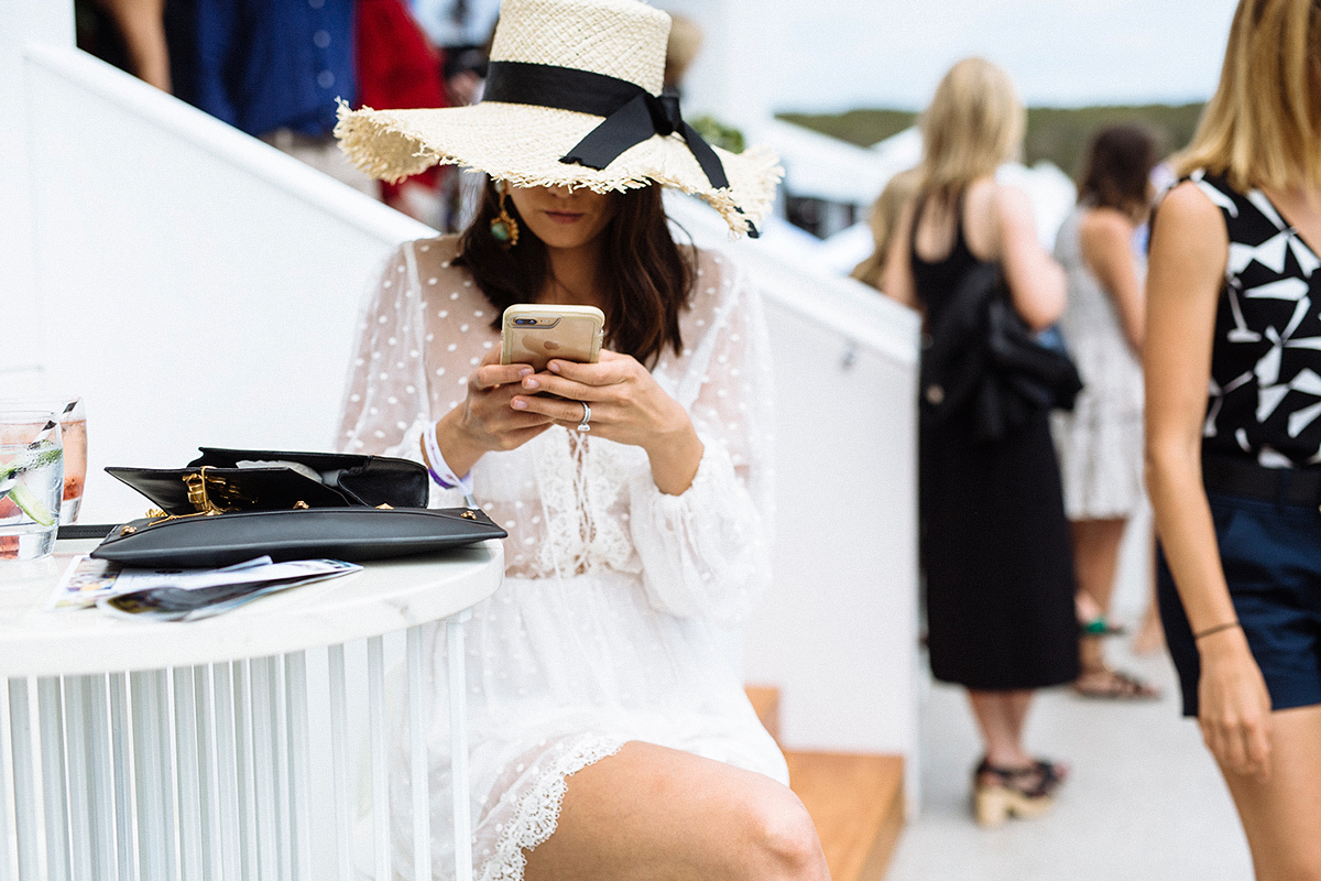 Model wearing white lace dress and oversized straw hat at the polo