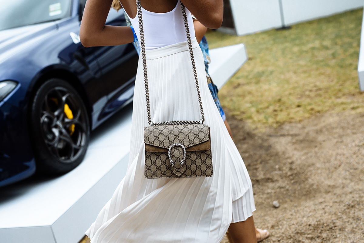 Model wearing Gucci bag as part of her polo outfit