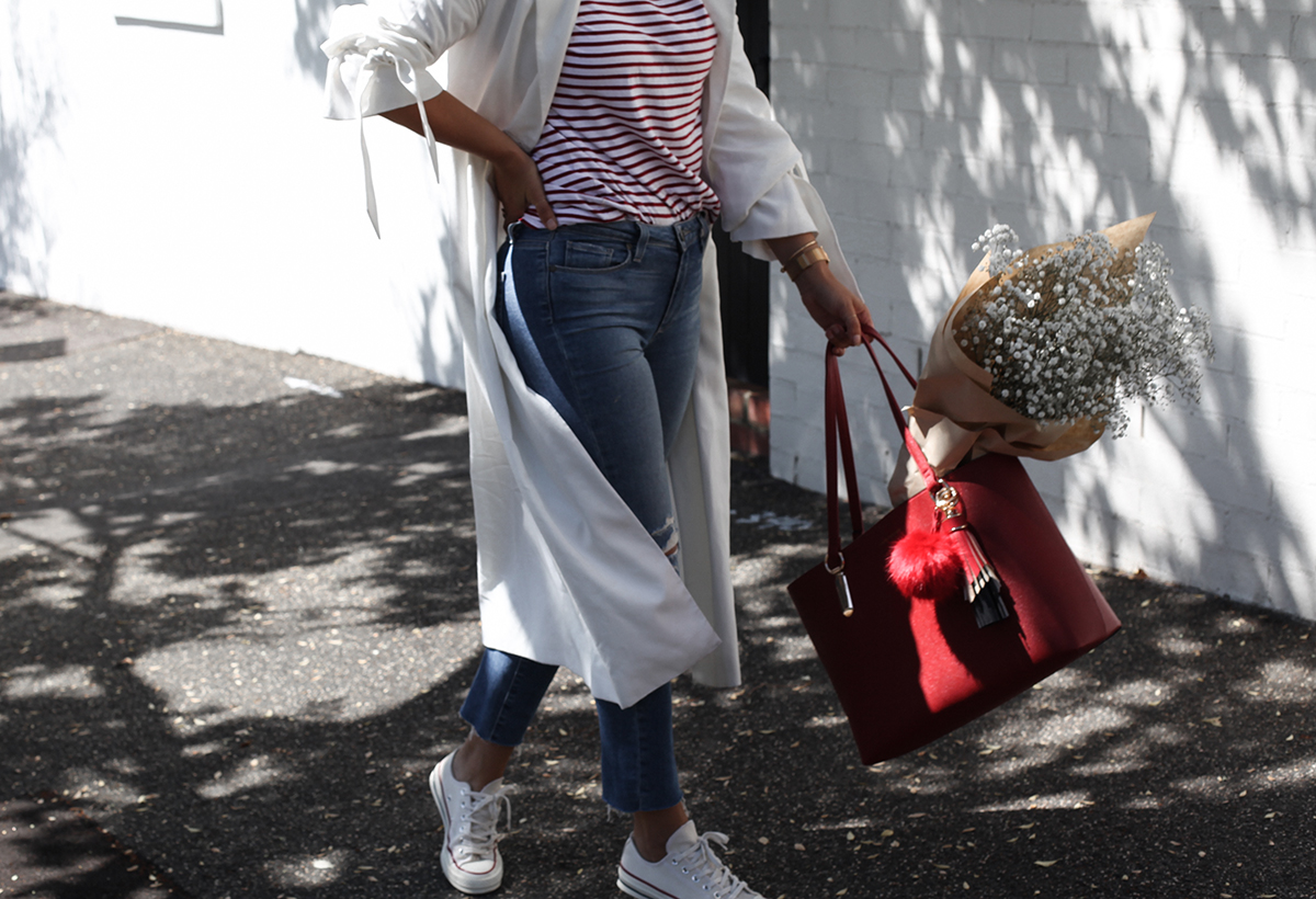 See Want Shop blogger Lisa Hamilton styling a red tote bag with a white trench coat, stripe tee & ripped jeans