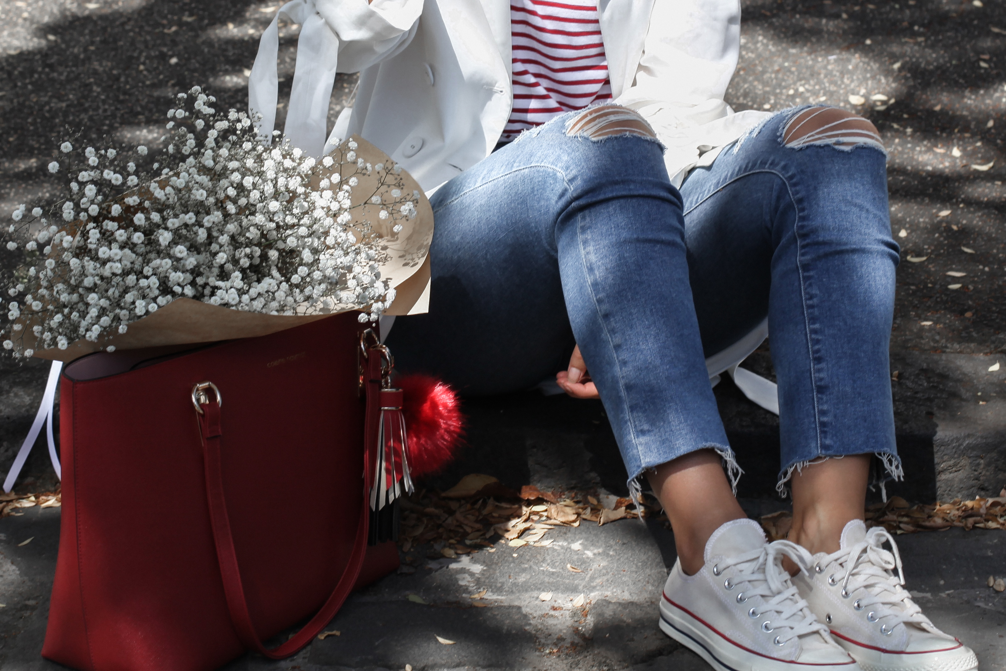 See Want Shop blogger Lisa Hamilton styling a red tote bag with ripped jeans & converse all star sneakers.