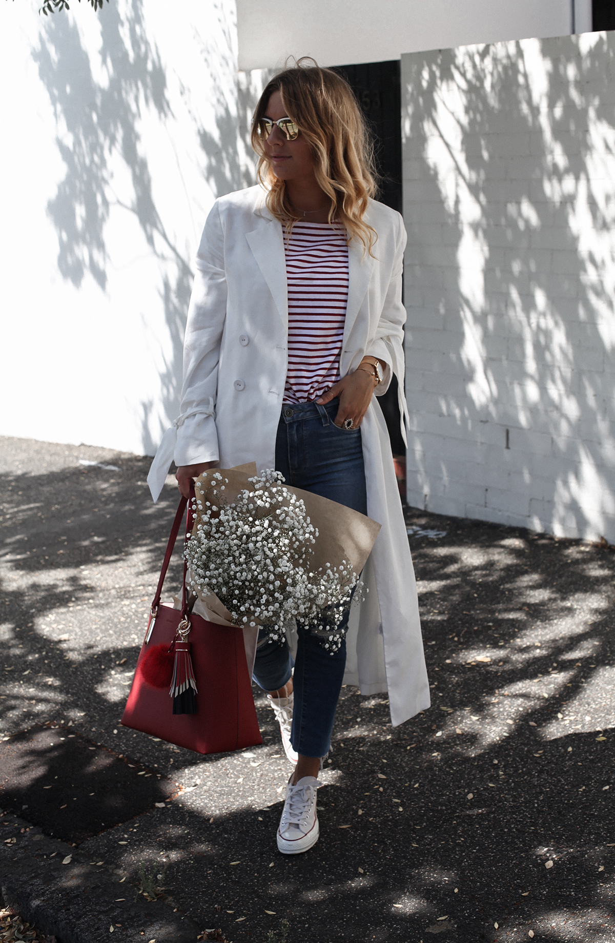 See Want Shop blogger Lisa Hamilton styling a red tote bag with a white trench coat & ripped jeans