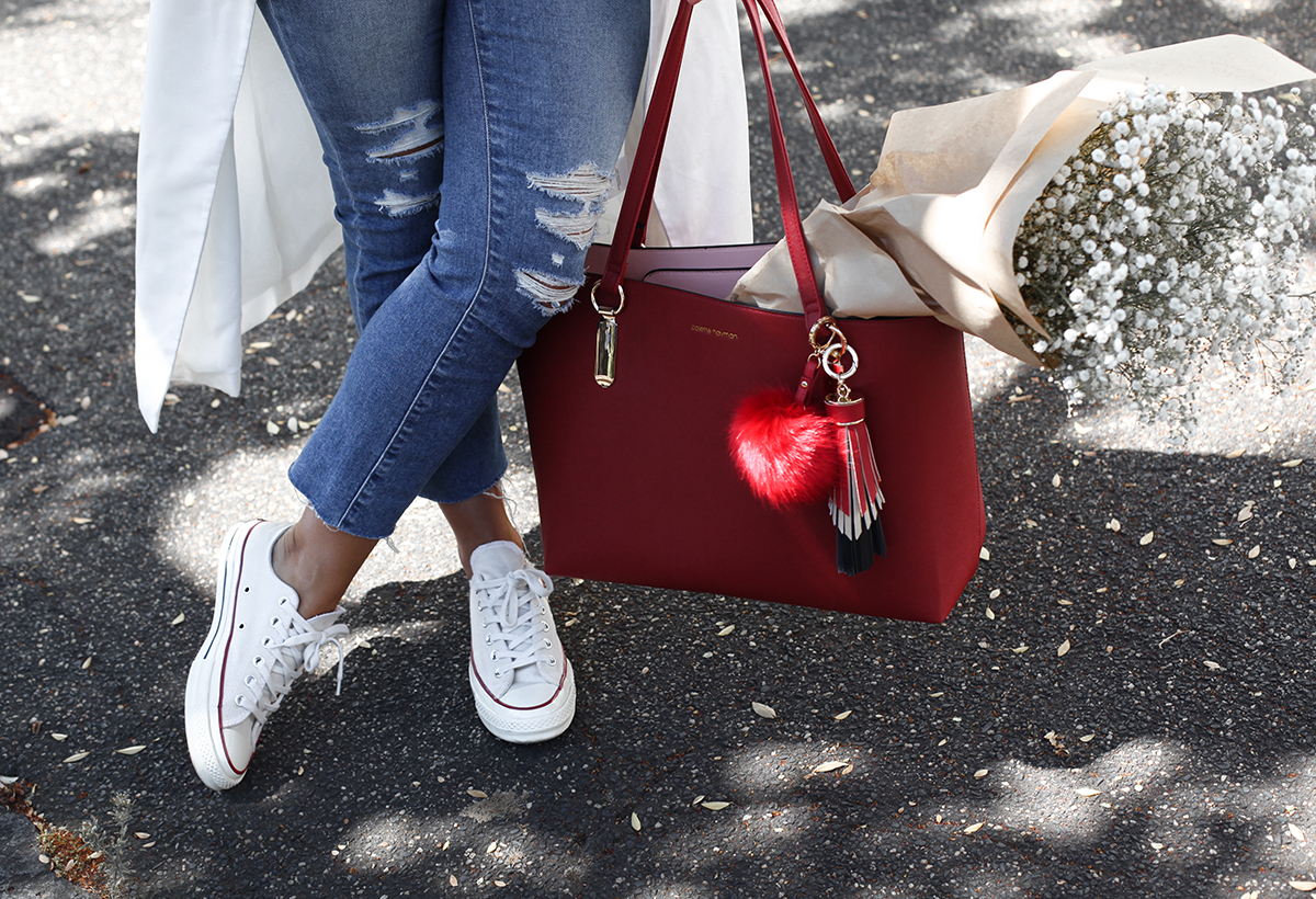 See Want Shop blogger Lisa Hamilton styling a red tote bag with pom-pom bag accessories, converse all stars & ripped jeans