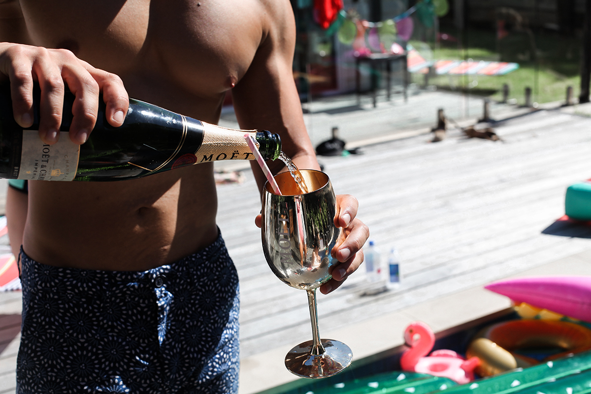 Topless waiter pouring a Moet & Chandon champagne goblet at a Bachelorette Party