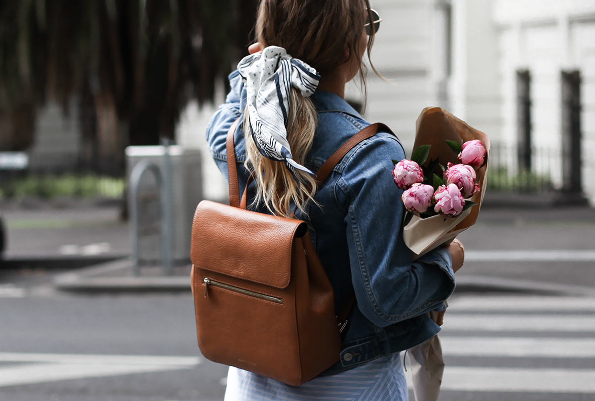 tan leather backpack and denim jacket
