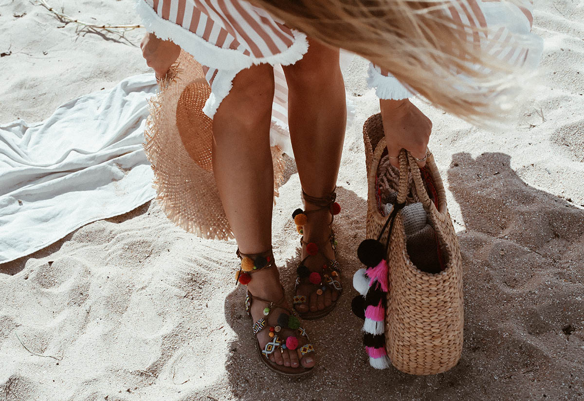 wearing pom-pom sandals from Etsy at the beach